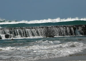The return of the tide overflowing a basalt rock pool wall - Mozambique
